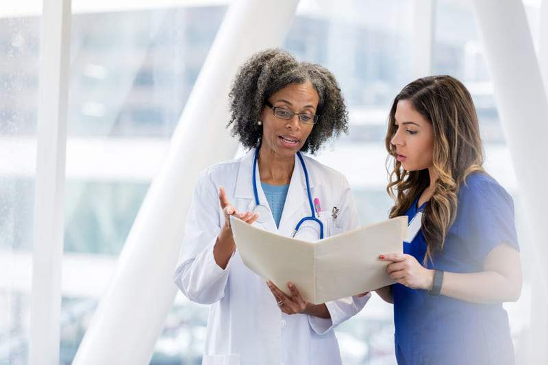 Doctor Reviews Certification With Employee 31