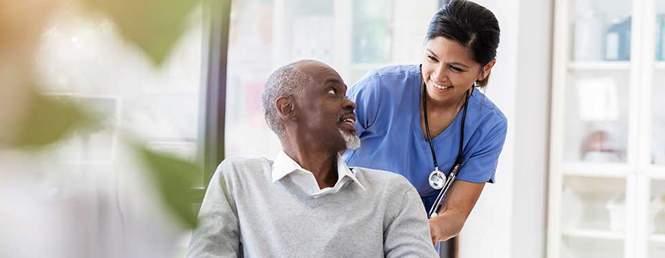Patient Care Tech Helping Patient