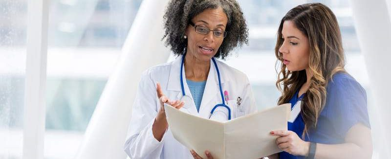 Doctor Reviews Certification With Employee 3